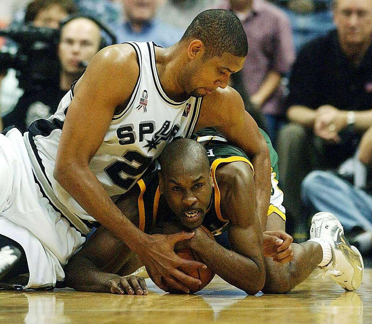 Spurs Tim Duncan and Seattle Gary Payton struggle for the ball during fourth period action at the Alamodome Monday April 22, 2002. WILLIAM LUTHER/STAFF