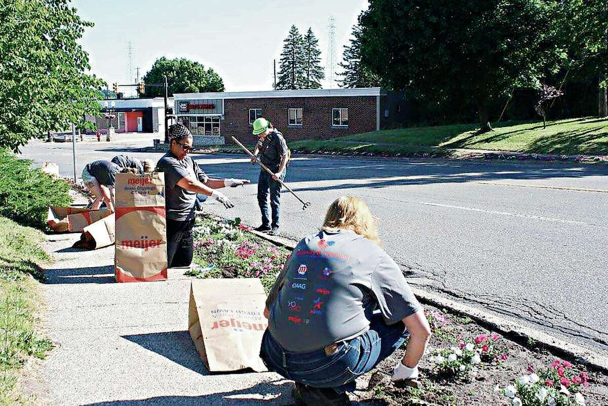 Volunteers arrived as part of Meijer's Stronger Together initiative and weeded the entire Blossom Boulevard on Tuesday.