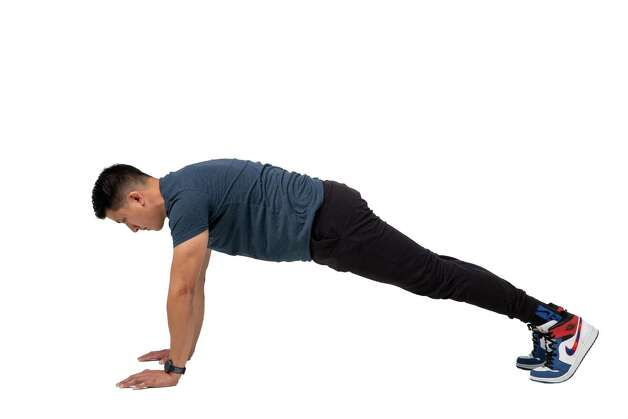 Start in a plank position with your hands on the ground directly beneath your shoulders, distributing the weight evenly between your hands and toes. Keep your back flat, stomach muscles tight and head in alignment. Photo: Godofredo A. Vásquez, Houston Chronicle / Staff Photographer / © 2021 Houston Chronicle