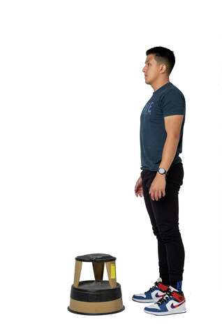 Find a short bench or something similar to step on. Start by standing straight with your feet hip-width apart and both arms relaxed at your sides. Photo: Godofredo A. Vásquez, Houston Chronicle / Staff Photographer / © 2021 Houston Chronicle
