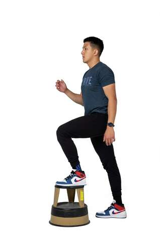 Step onto the bench with your left leg, press through the foot to bring your body on top. Stand tall with your legs fully extended. Photo: Godofredo A. Vásquez, Houston Chronicle / Staff Photographer / © 2021 Houston Chronicle