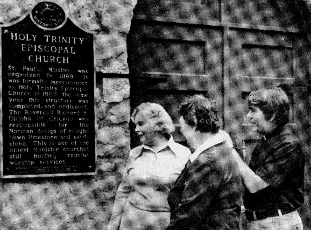 Father Peter Wenner, of Holy Trinity Episcopal Church, and church members (from left) Marion Henry and Irene Housworth read the marker granted to the church by the State of Michigan for attaining historical site status. The photo was published in the News Advocate on June 18, 1981. (Manistee County Historical Museum photo)