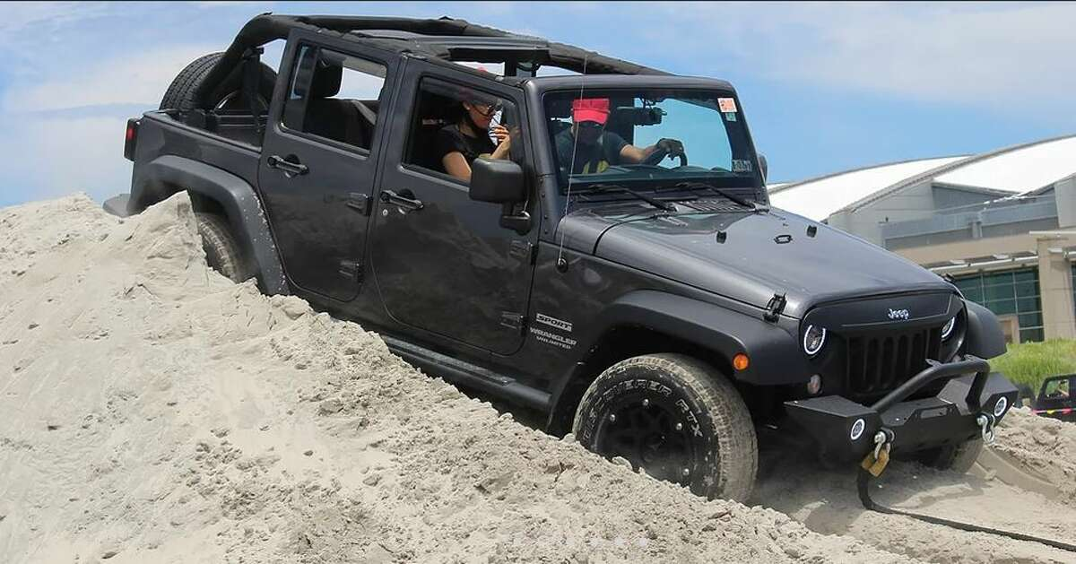 """Jeeps, like this one pictured in a beachfront sand dune, will be in abundance at a Lake George """"Jeep Invasion"""" this summer."""