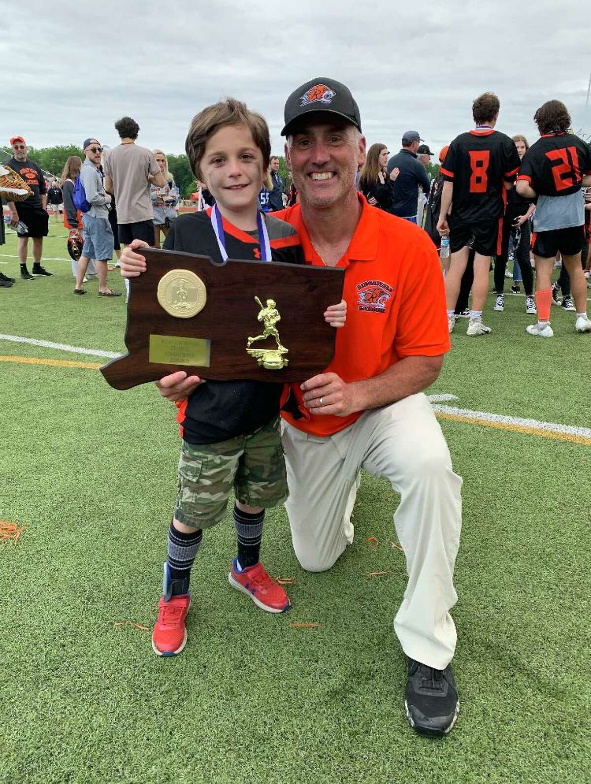 Conner Curran holds the state championship plaque alongside head lacrosse coach Roy Colsey.