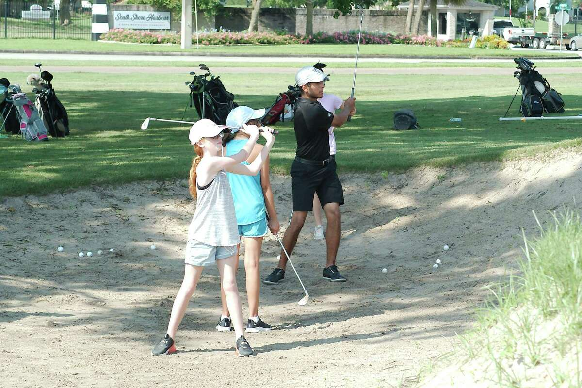 Cailey Mitchell and Kiley McManus watch as Clear Creek golfer J.P. Vallejo demonstrates how to hit a bunker shot at the Wildcat golf camp held at South Shore Harbor Country Club in League City.