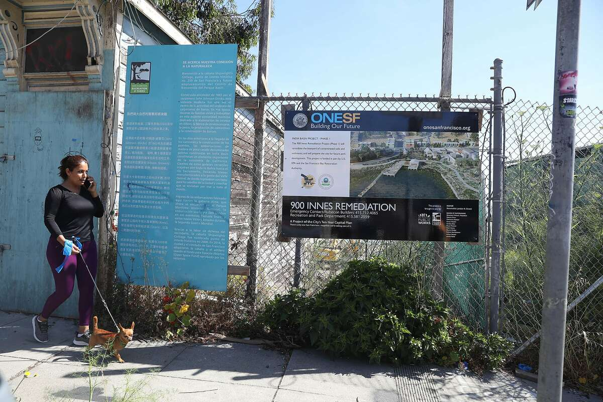 A pedestrian walks past a sign about the 900 Innes Remediation Project while walking on Innes Street on Wednesday, June 16, 2021 in San Francisco, Calif.