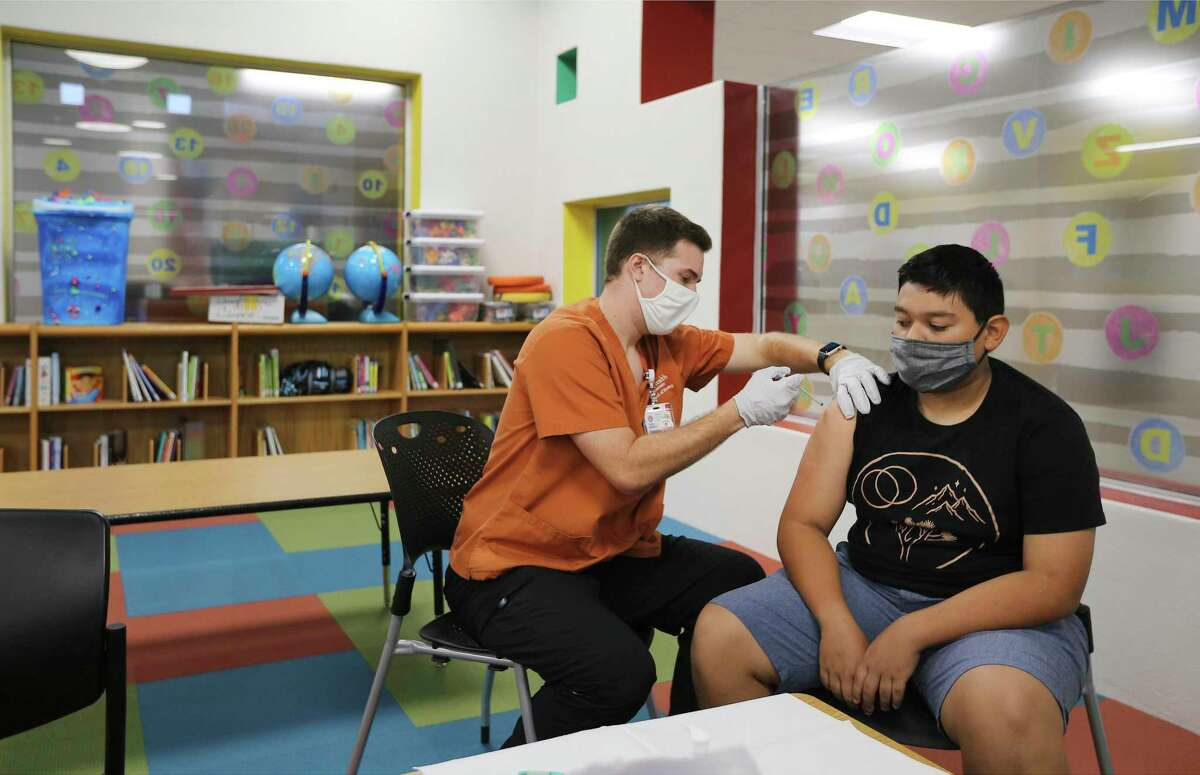 Alexander Garcia, 13, receives a Pfizer Covid-19 vaccine from UT Health student nurse Trey Maxey (left) at Miguel Menchaca Early Childhood Center at Southside ISD on Monday, June 7, 2021.