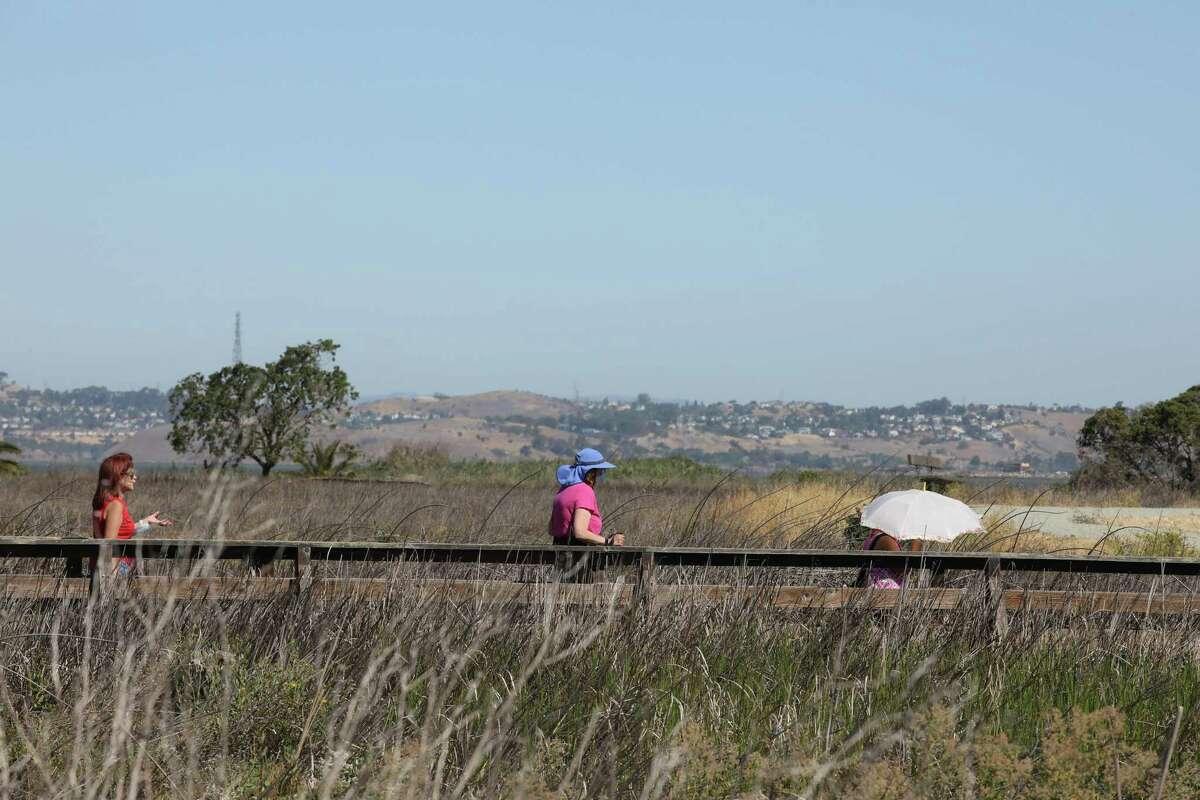 Folks walk on a trail at the Martinez Regional Shoreline on Wednesday, June 16, 2021, in Martinez, Calif.