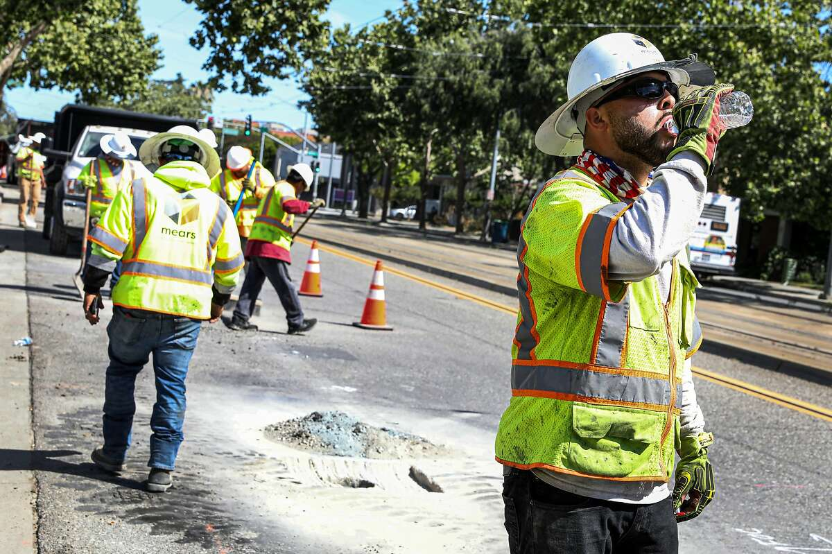Joey Valles drinks from bottled water while working to install a telecommunication line on First Street in San Jose, Calif. on Wednesday, June 16, 2021. The National Weather Service is issuing heat warnings for most of the Bay Area and surrounding counties for the next several days.
