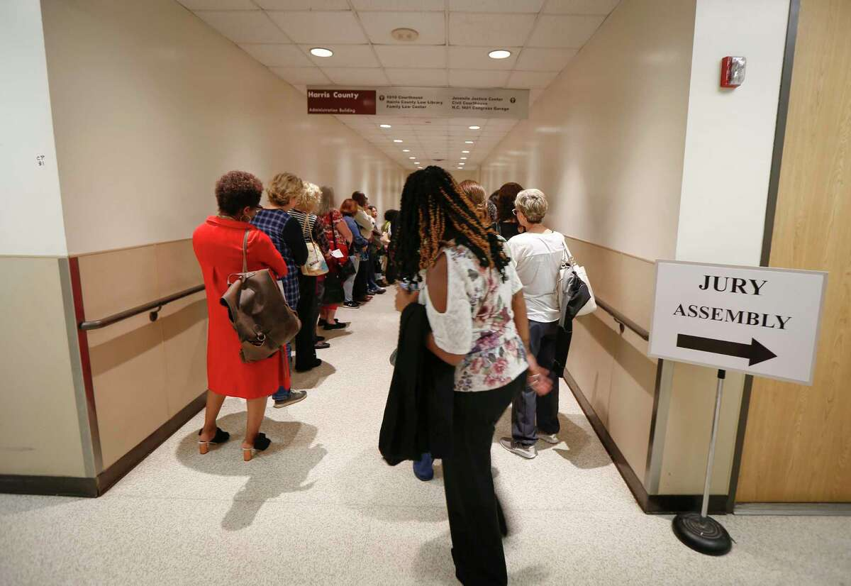 Harris County residents wait in the tunnel hallway for instructions before heading for their jury duty Wednesday, Jan. 15, 2020, in Houston. As more and more judges physically return to their courtrooms and hold jury trials in person, virtual trials are still allowed under pandemic-era emergency orders from the state's high court.