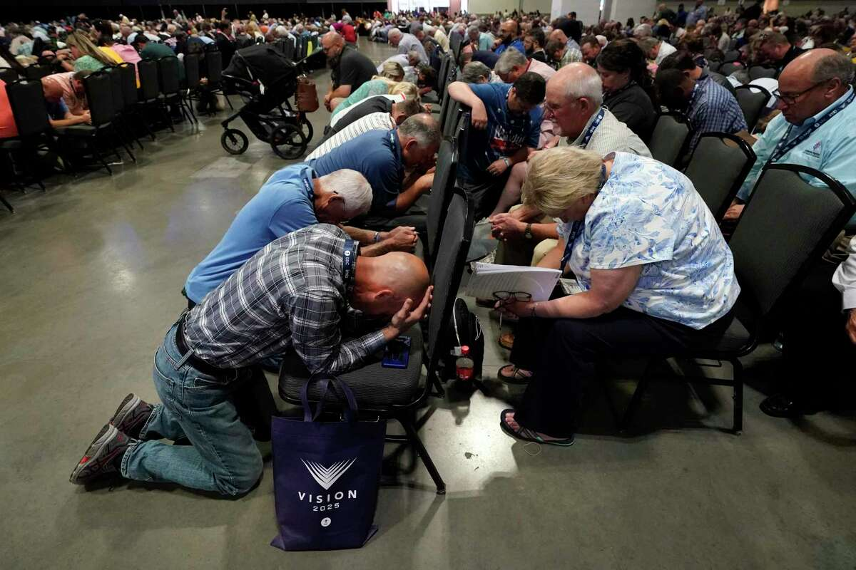 People pray during the annual Southern Baptist Convention meeting Tuesday, June 15, 2021, in Nashville, Tenn. (AP Photo/Mark Humphrey)