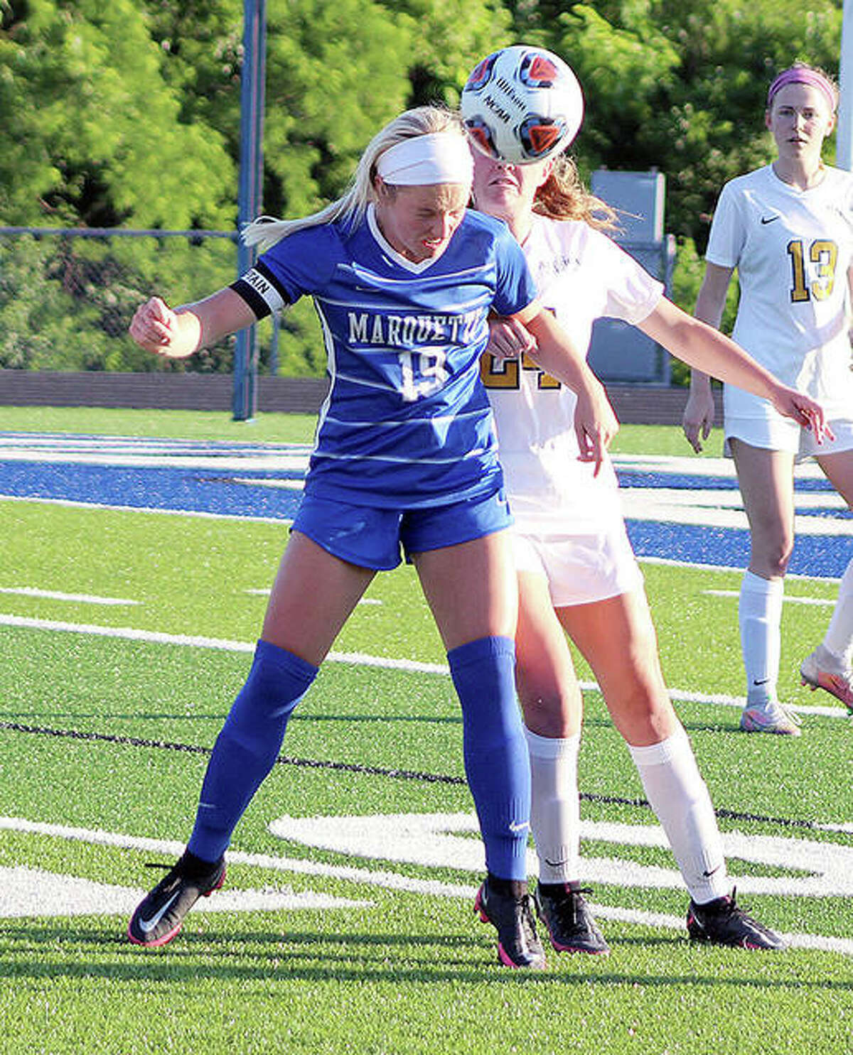 Emma Anselm of Marquette (19) and Althoff's Hope Schmitt battle for possession of the ball Tuesday at the Columbia Class 1A Super-Sectional game.