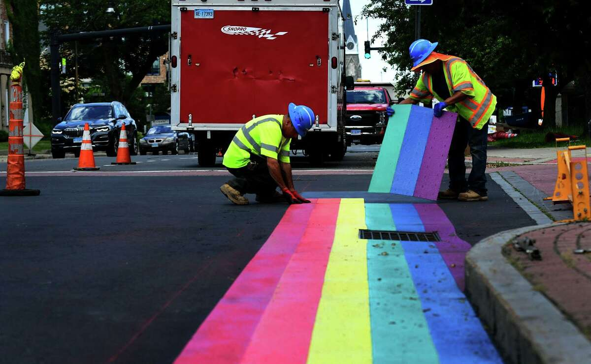 Workers with Laydon Industries lay a thermoplastic rainbow border to the crosswalk on West Ave at Mathews Park Wednesday, June16, 2021, in Norwalk, Conn.