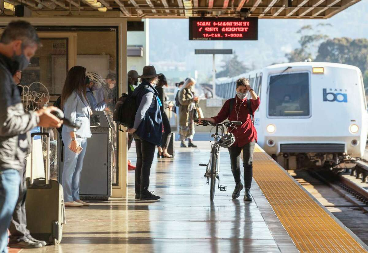 Morning commuters wear masks while waiting for a San Francisco bound BART train at MacArthur station in Oakland on June 15, 2021.