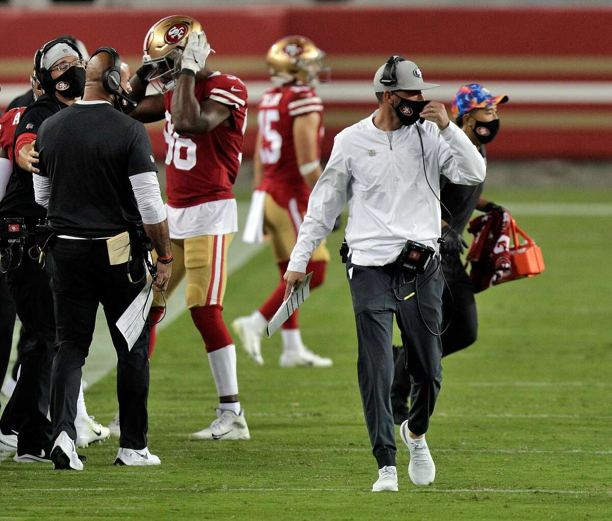 NFL coaches such as the 49ers' Kyle Shanahan no longer need to wear face coverings during games if they are fully vaccinated, according to Wednesday's announcement by the league. Shanahan is shown adjusting his mask during a home game against Philadelphia on Oct. 4, 2020.