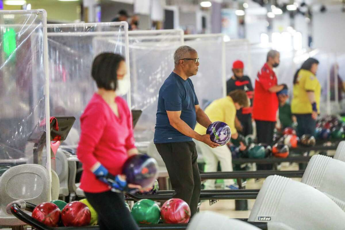 Rodney Garrick (center) prepares to bowl the Classic Bowling Center without wearing a mask in Daly City. Sacramento County became the latest California county to urge all residents to wear face masks indoors as COVID-19 cases spike.