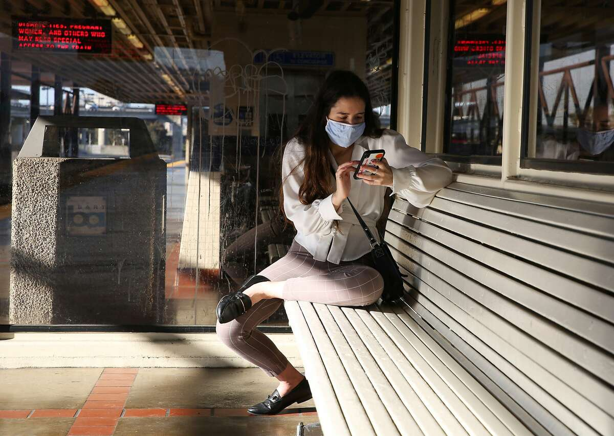 Emily Filkin wears a mask as she waits for the train toward San Francisco at MacArthur Station in Oakland on the day California lifted nearly all its pandemic restrictions on Tuesday, June 15, 2021.