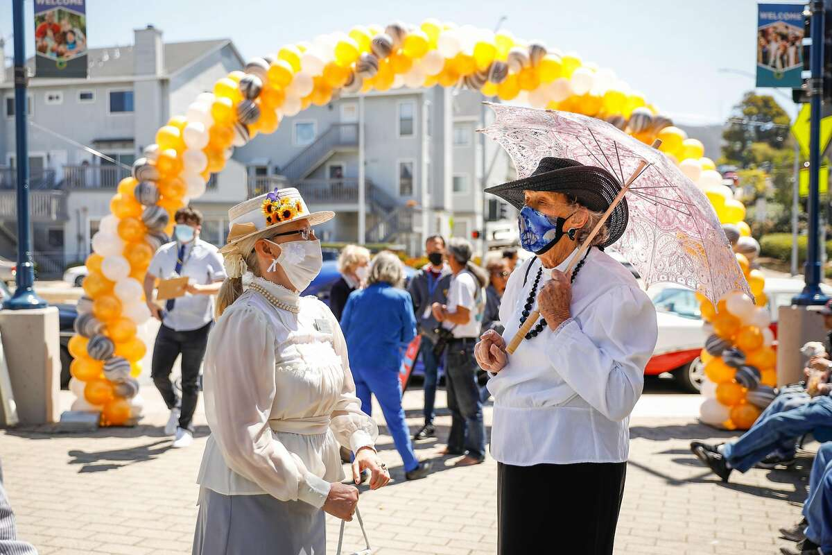 """Tatiana Elliston (left) and Laura Peterhans (right), who are dressed to look like women from the 1918 pandemic, chat at the """"Reopening of the State Celebration"""" in Colma, California on Tuesday, June 15, 2021. The party was to celebrate the first day of being able to operate indoors and outdoors without masks for those that are vaccinated."""