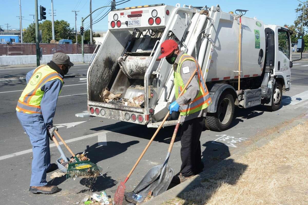 Ayinde Osayaba and David Conti Jr. clean up trash in Oakland, June 2021.