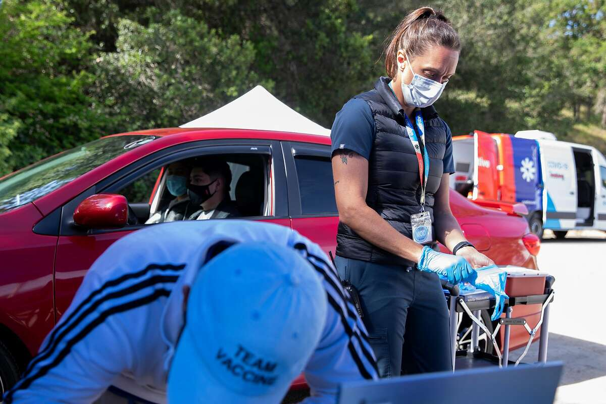 Registered nurse Becky Dodds puts on gloves before giving Kevin Vasquez his first dose of the Moderna COVID-19 vaccine at a Curative vaccination pop-up in the parking lot of Hamilton Community Center in Novato, Calif. Friday, April 30, 2021.