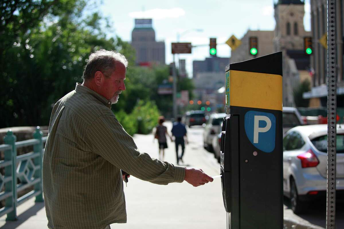 Jeff Talley, 61, pays the meter at the Commerce Street parking lot downtown. The city normally offers free parking downtown from 5 p.m. to 2 a.m. every Tuesday through its Downtown Tuesday program. But it's suspending the program during Fiesta.