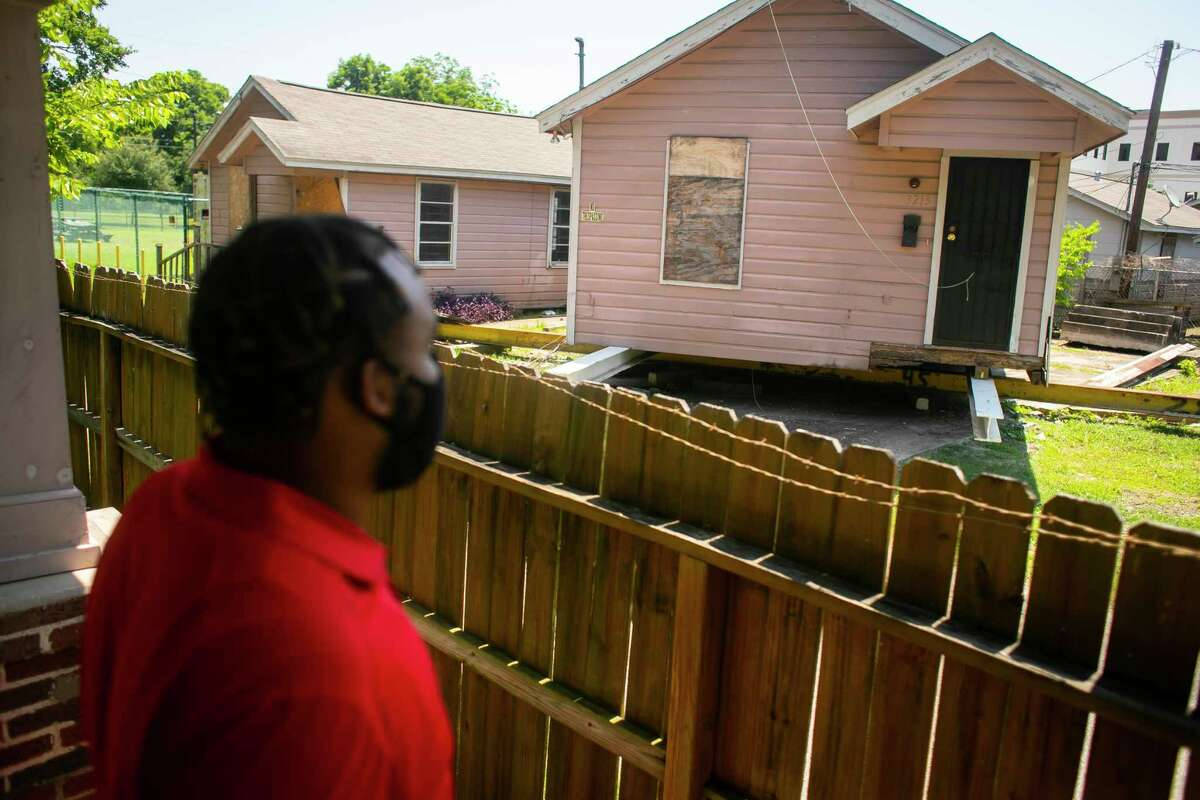 Benjamin Smith looks out onto one of the properties owned by Change Happens CDC, a local nonprofit founded by his father, Rev. Leslie Smith, on Wednesday, June 16, 2021. Change Happens CDC buys, moves and builds properties to ensure residents in Third Ward have affordable housing options.