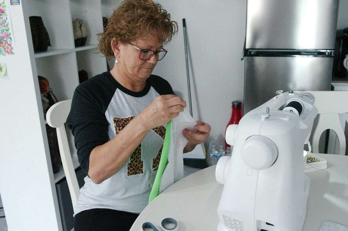 """Heidi Schubert pieces together old T-shirts to make a keepsake blanket for a customer. """"Everybody has a lot of T-shirts,"""" she says. """"We can make a blanket and hand that blanket down to the next generation so that they have something to remember you by."""""""