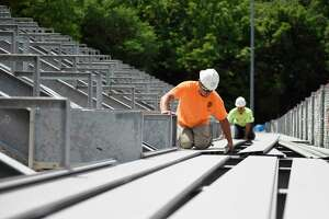 Zach Carroll lays down aluminum flooring on the bleachers at Greenwich High School's Cardinal Stadium in Greenwich, Conn. Wednesday, June 16, 2021. While the bleachers will not be done in time for next week's graduation, the beginning of the physical construction marks a major milestone in the Cardinal Stadium improvement project.