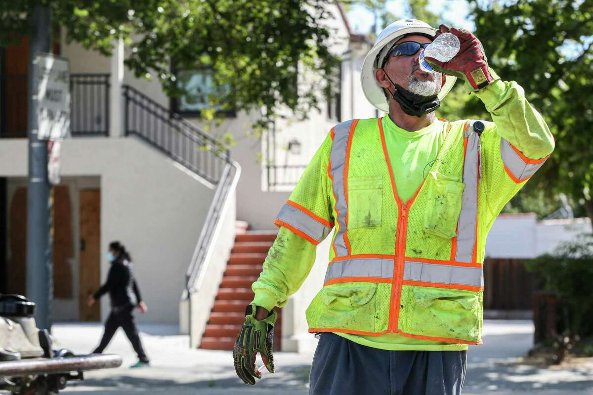 Luciano Salazar drinks from bottled water while working to install a telecommunication line on First Street toward downtown San Jose, Calif., on Wednesday, June 16.