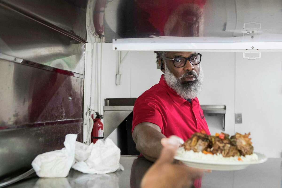 Troy Williams passes a plate of oxtails through the kitchen window as he fills an order at Alfreda's Soul Food Tuesday, May 11, 2021 in Houston. Many small businesses didn't survive the pandemic, minority and women-owned businesses were particularly hard hit. Despite the odds, Troy and Marguerite Williams' kept their restaurant, Alfreda's Soul Food, open.