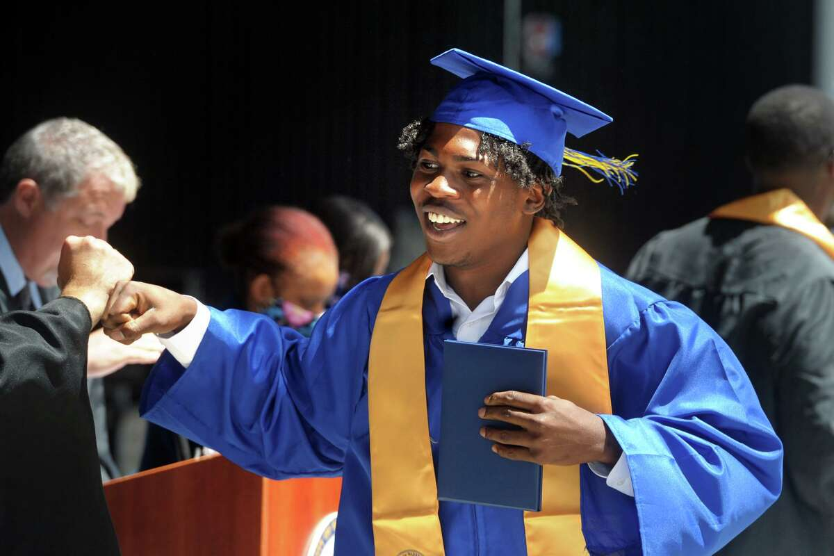 Gabriy'el Fraser receives his diploma during graduation for the Warren Harding High School Class of 2021, at the Hartford Healthcare Amphitheater in Bridgeport, Conn. June 16, 2021.