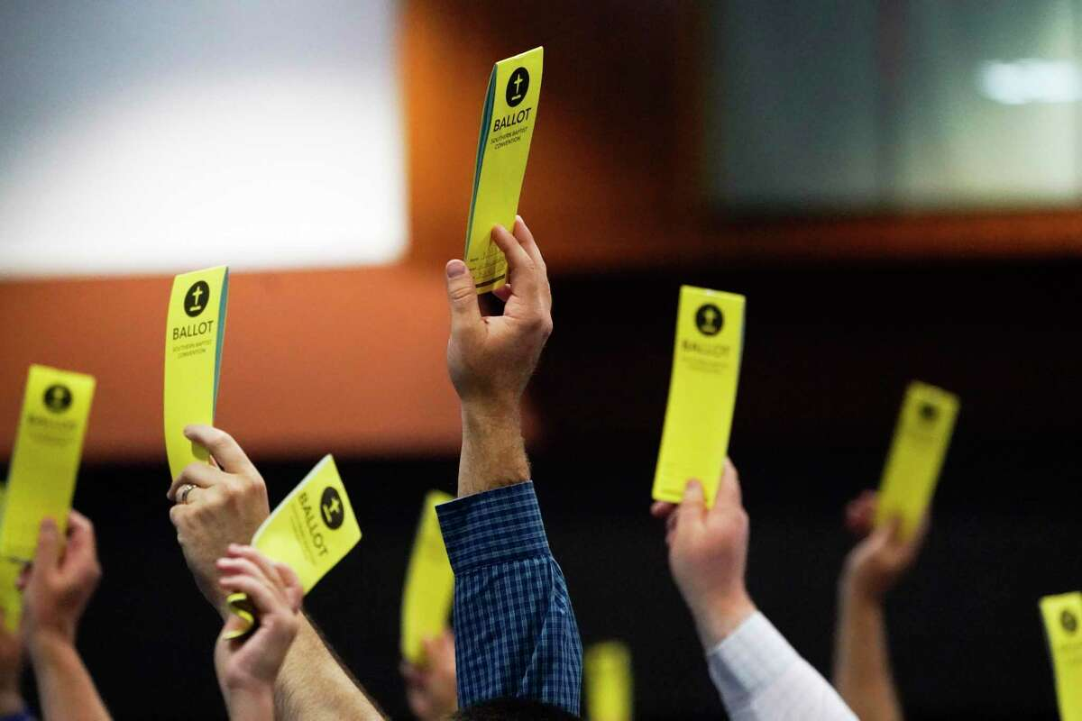People signify their vote on a motion during the annual Southern Baptist Convention meeting Wednesday, June 16, 2021, in Nashville, Tenn. (AP Photo/Mark Humphrey)