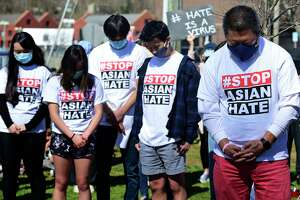 Over a hundred residents bow their heads with State Representative Tony Hwang they turned out to peacefully protest on Jesup Green Saturday, March 27, 2021, in Westport, Conn. The protesters gathered in solidarity with the AAPI community in opposition to the rise of hate crimes against that Asians and Pacific Islanders.