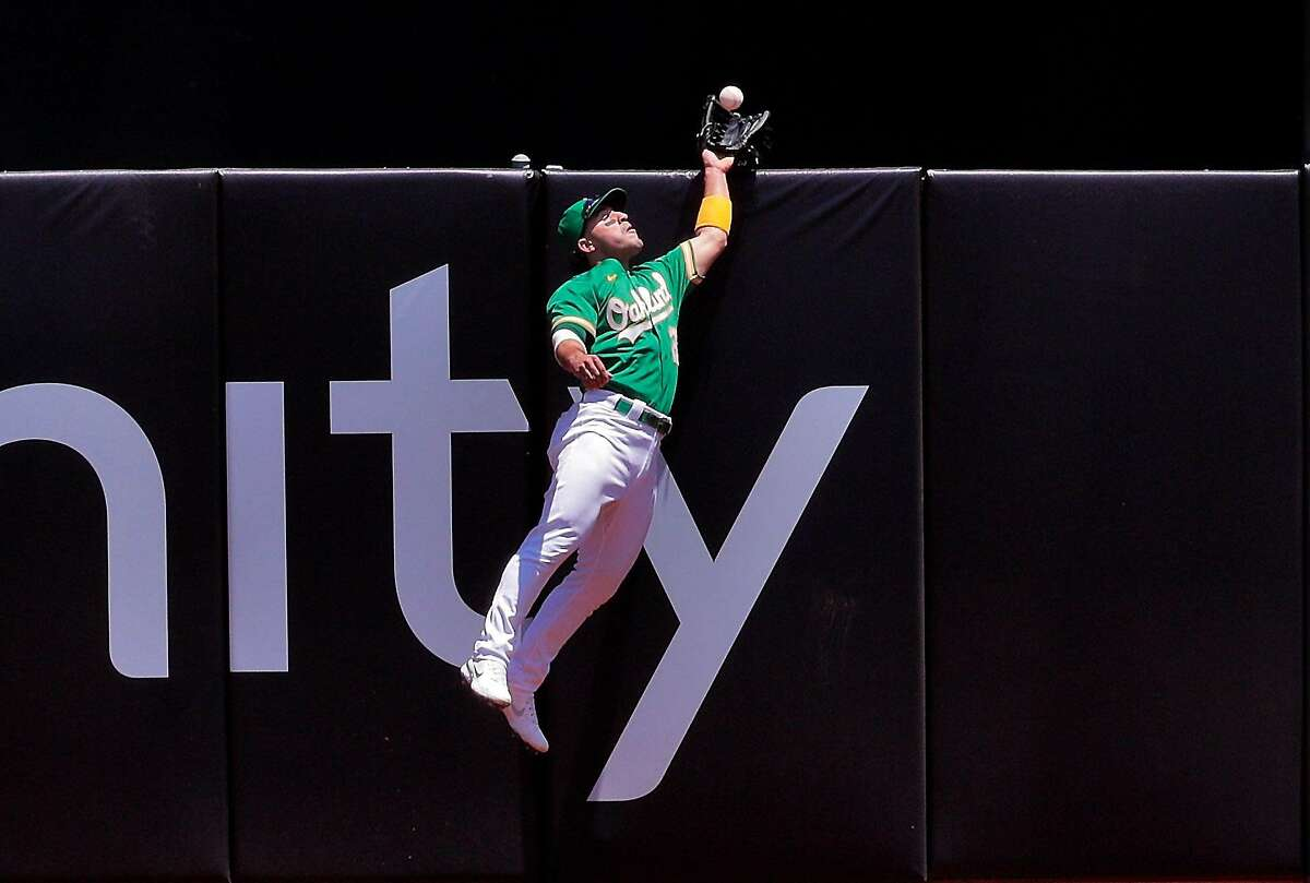 Top: Laureano makes a two-footed leap to the top of the wall to snare a drive from Justin Upton in the fourth.