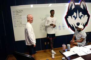 UConn men's basketball coach Dan Hurley, left, and Associate Head Coach Kimani Young, right, meet with incoming freshman Samson Johnson for the first time before practice at the Werth Family UConn Basketball Champions Center on the UConn main campus in Storrs, Conn. Wednesday, June 9, 2021.