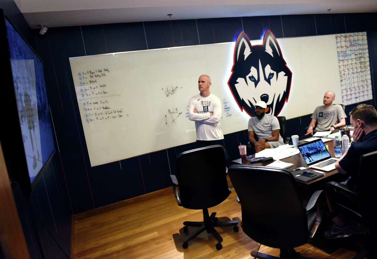 UConn men's basketball coach Dan Hurley, left, watches video of recruits with assistant coaches before practice at the Werth Family UConn Basketball Champions Center on the UConn main campus in Storrs, Conn. Wednesday, June 9, 2021.