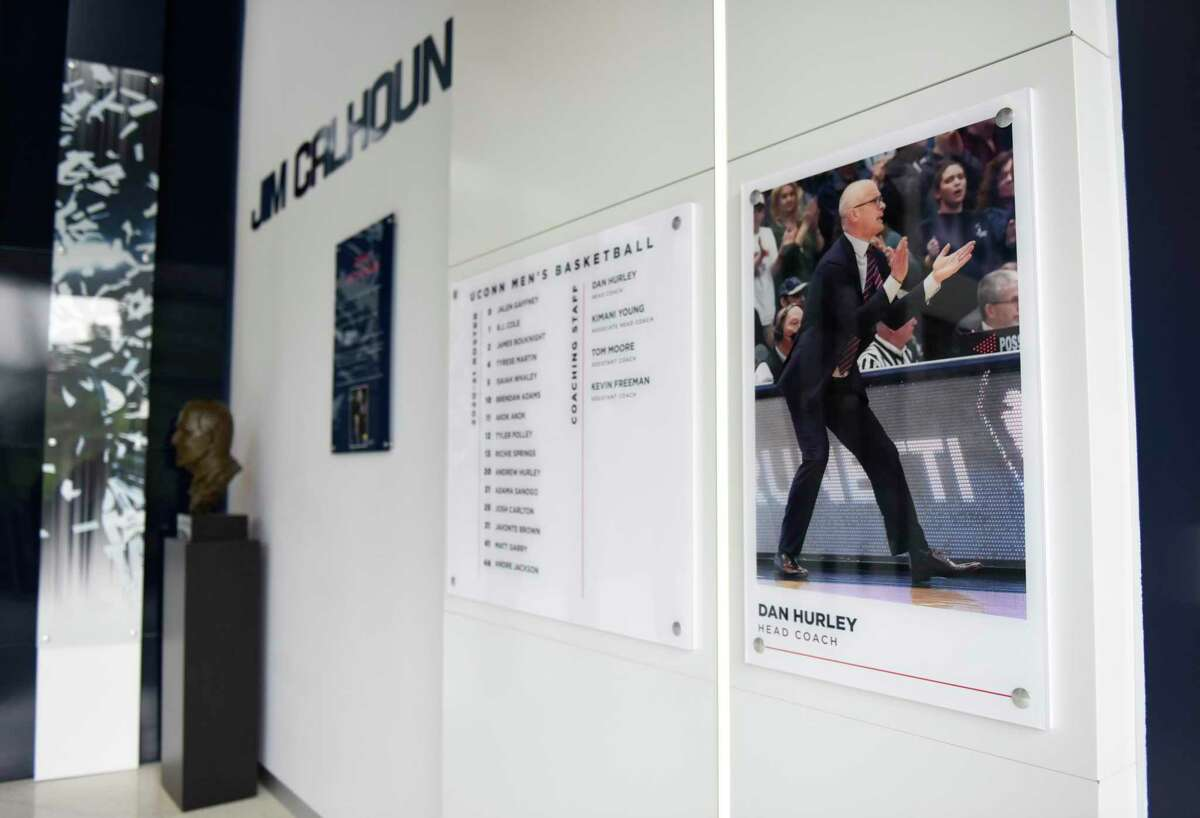 A photo of current coach Dan Hurley is displayed next to a bust and plaque of former coach Jim Calhoun at the men's basketball practice facility in the Werth Family UConn Basketball Champions Center on the UConn main campus in Storrs, Conn., photographed on Wednesday, June 9, 2021.