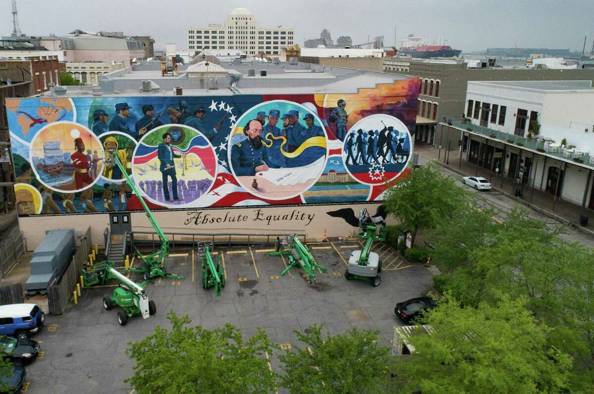 Artists finish final details on a 5,000-square-foot mural at the Osterman Building in Galveston in April. The artwork commemorates Juneteenth, when an Army general on June 19, 1865, announced in Galveston that slaves had been emancipated.