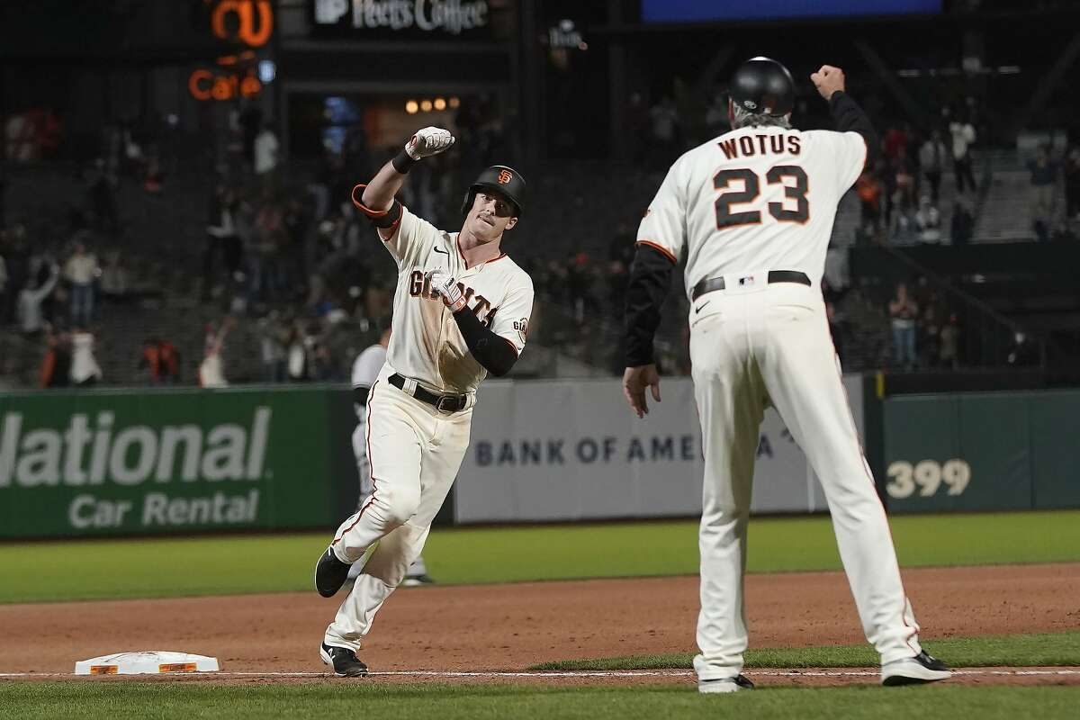 San Francisco Giants' Mike Yastrzemski, left, is congratulated by third base coach Ron Wotus (23) after hitting a grand slam during the eighth inning of a baseball game against the Arizona Diamondbacks in San Francisco, Tuesday, June 15, 2021. (AP Photo/Jeff Chiu)