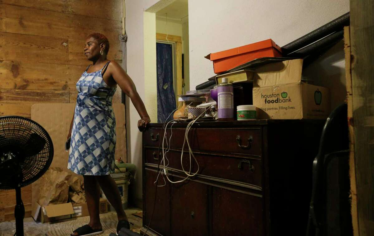 """Sandra Edwards, 55, shows the interior of her steamy house Wednesday, June 16, 2021, at in Houston. The house was flooded during Hurricane Harvey, and it is still going through rebuilding. Before Harvey, she had air conditioning system installed in the house, but now she only has a window unit air conditioner. """"I'm basically confined in (that) room,"""" she said."""