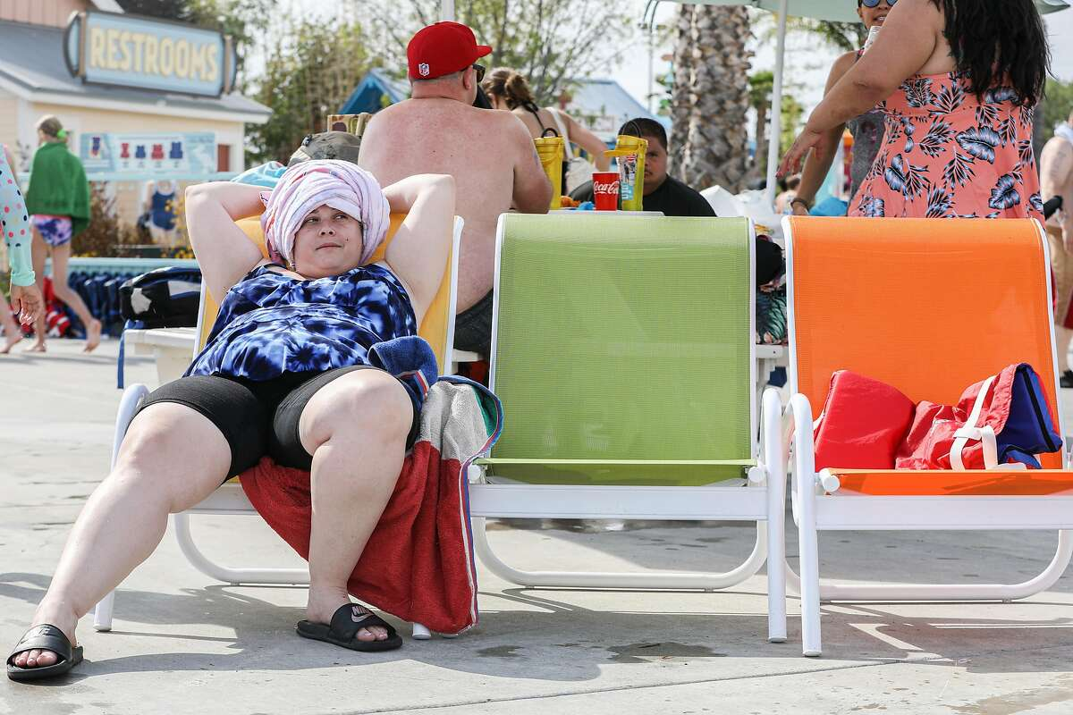 Ashley Giovacchini lounges near the pool at South Bay Shores water park at California's Great America in Santa Clara, Calif. on Wednesday, June 16, 2021. The water park opened on June 5 after having post poned their opening day last year due to the pandemic. The water park includes slides, a lazy river and wave pool offering solace to visitors beating the heat after the National Weather Service is issuing heat warnings for most of the Bay Area and surrounding counties for the next several days.