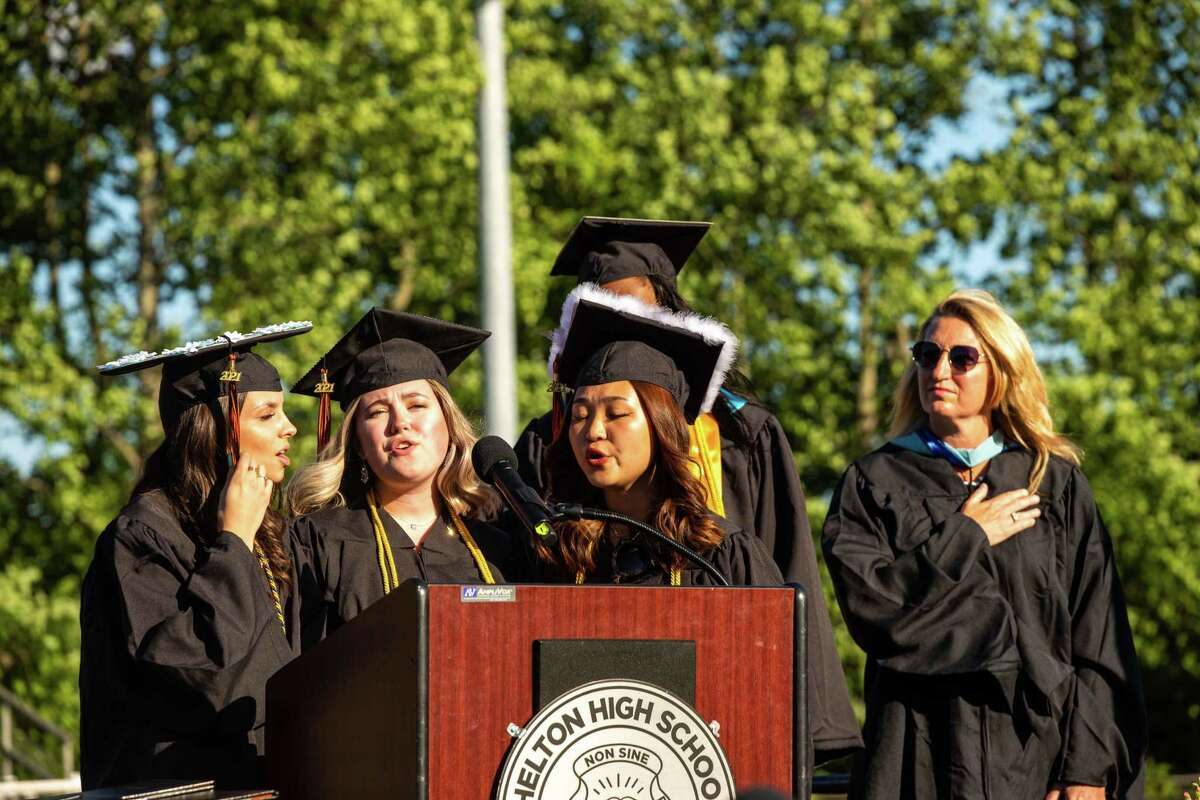 Shelton High School graduates Casey An, Brooke Doolan and Megan McCarthy sing the National Anthem during graduation for the Class of 2021 on Wednesday.