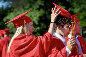 Amanda Manente, left, helps Kristopher Canhassi with his cap before the start of Wednesday's ceremony. Stratford High School Class of 2021 held its graduation ceremony at Penders Field at Longbrook Park in Stratford Wednesday, June 16, 2021.