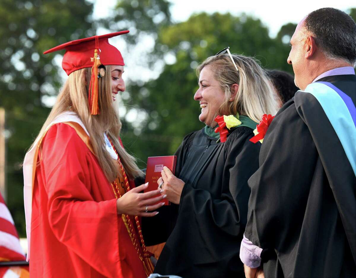 Ryann Wiltsie, right, accepts her diploma from her mother Amy Wiltsie, vice chairman of the Board of Education. Stratford High School Class of 2021 holds its graduation ceremony at Penders Field at Longbrook Park in Stratford Wednesday, June 16, 2021.