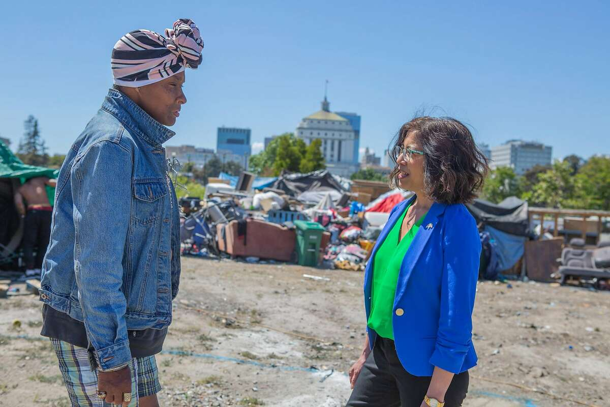 Oakland City Council Member Nikki Fortunato Bas (right) speaks with Krystal, a resident of the encampment near Lake Merritt, about the property being slated for the construction of a 24-story tower of market-rate condominiums by UrbanCore.