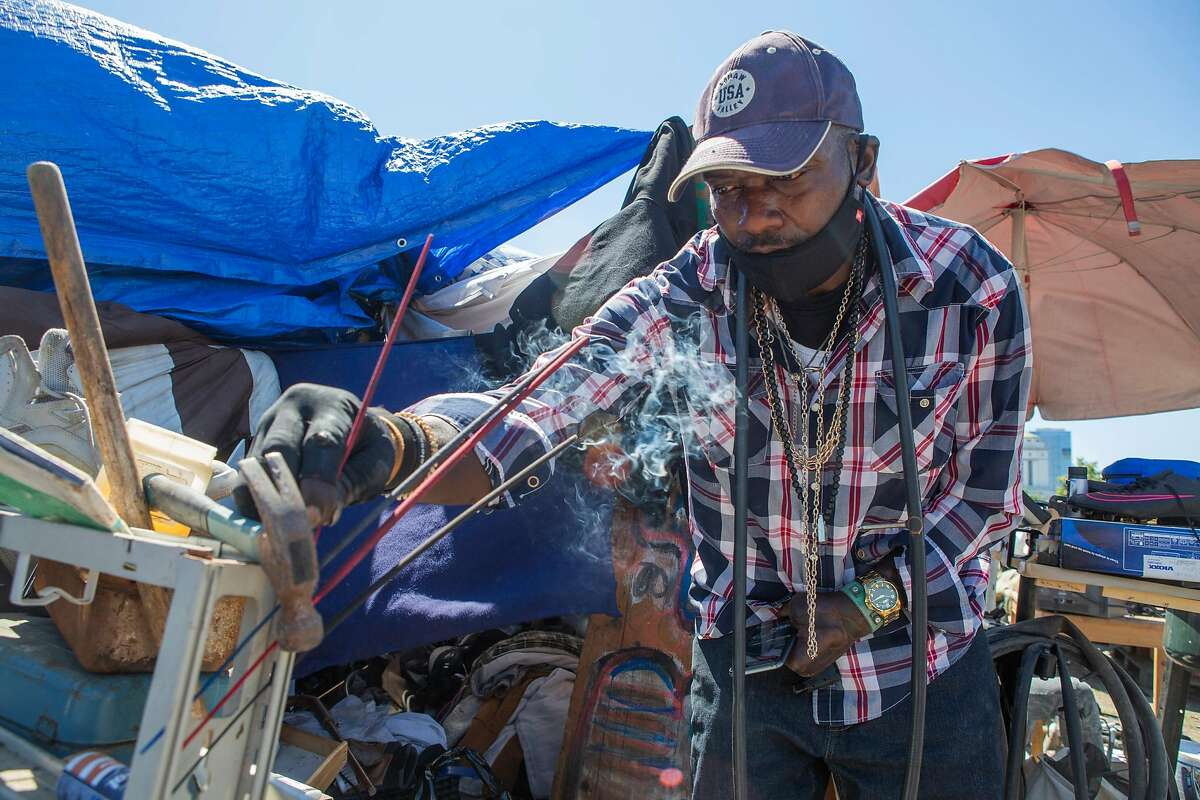 Mtulazaji lights an incense stick in front of his tent in Oakland. He has been residing at the encampment near Lake Merritt on and off for five years, and the lot has been slated for construction.