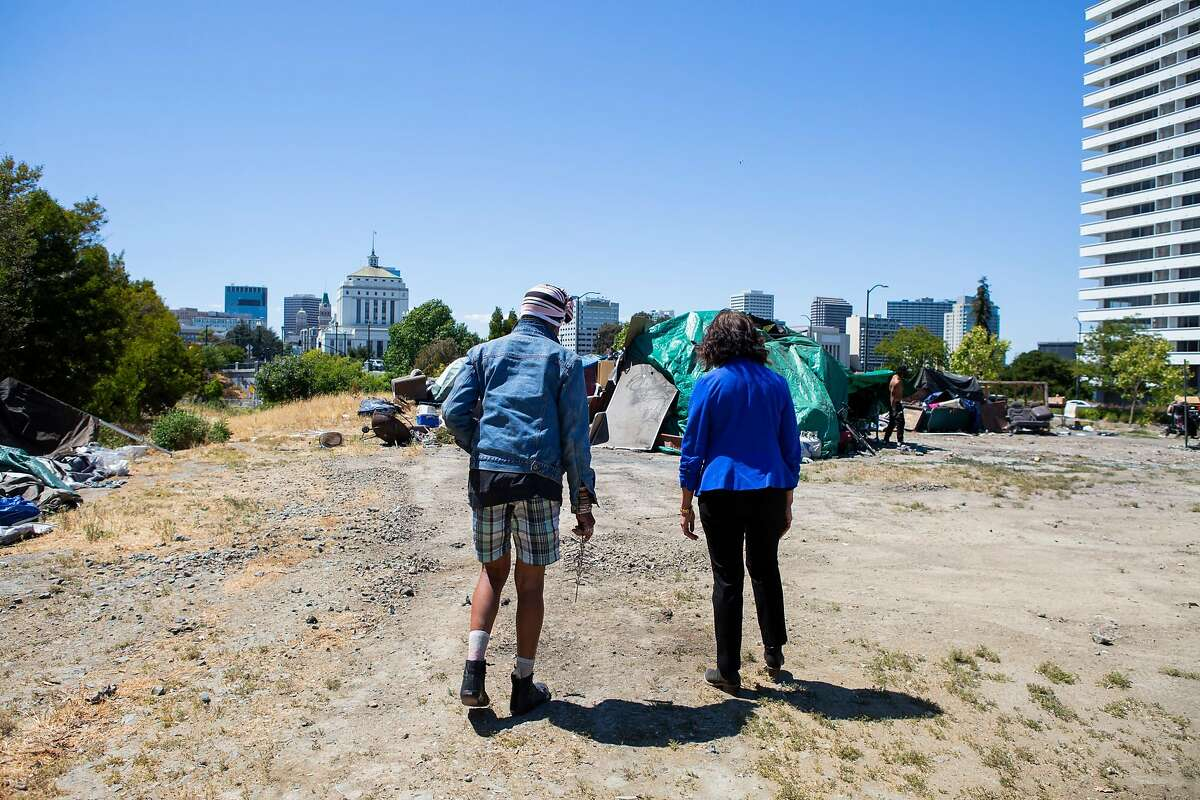 Oakland City Council Member Nikki Fortunato Bas (right) speaks with Krystal about the plans for the lot that the homeless woman has been residing on for the past year.
