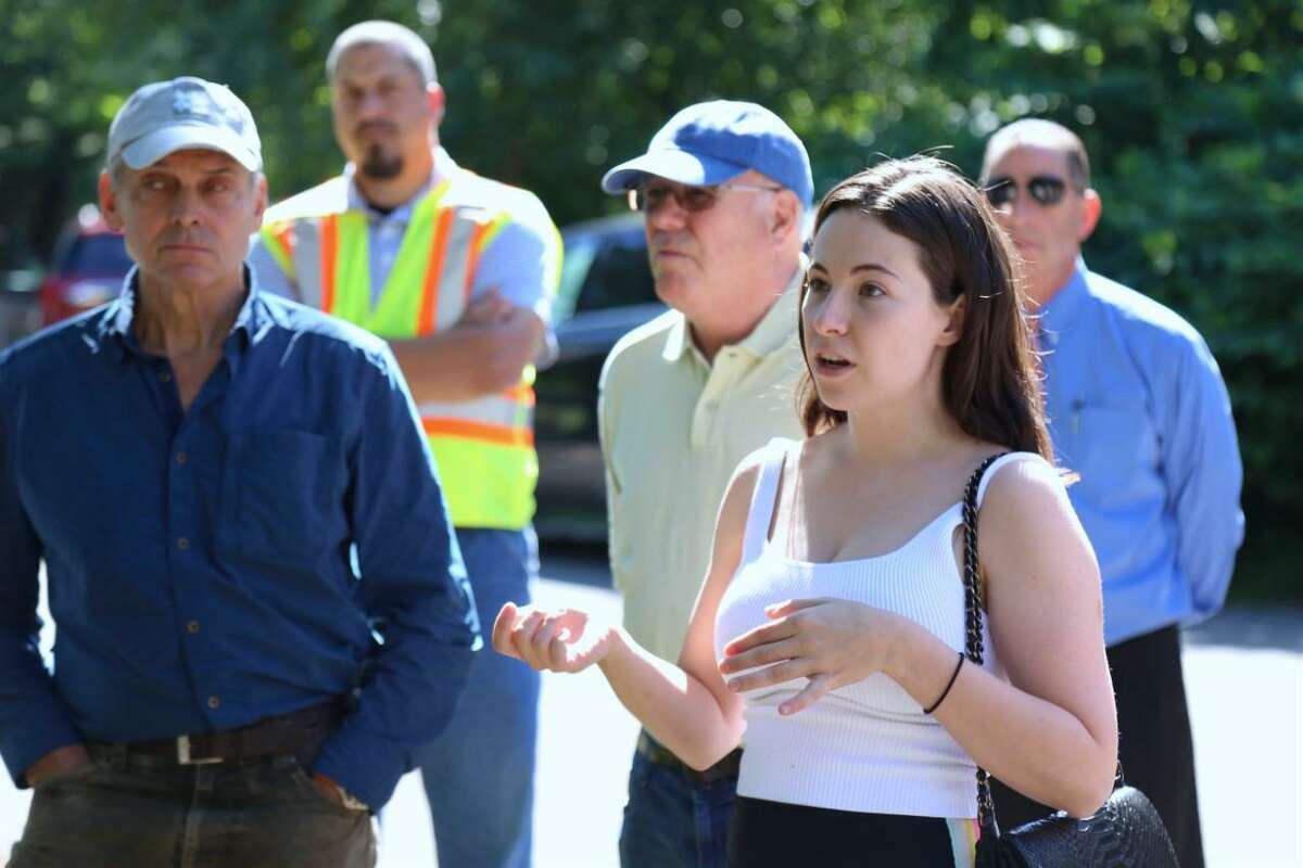 Neighbor Alba Dexheimer asks a question of Eversource officials Wednesday morning at a meeting at the cul de sac of Little Brook Road.