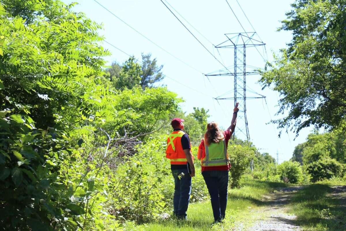 After hearing the sound of electrical arcing toward the end of Wednesday's meeting on Little Brook Road, Eversource personnel take a closer look along the power lines running between the dead-end street and the Metro North rail line.