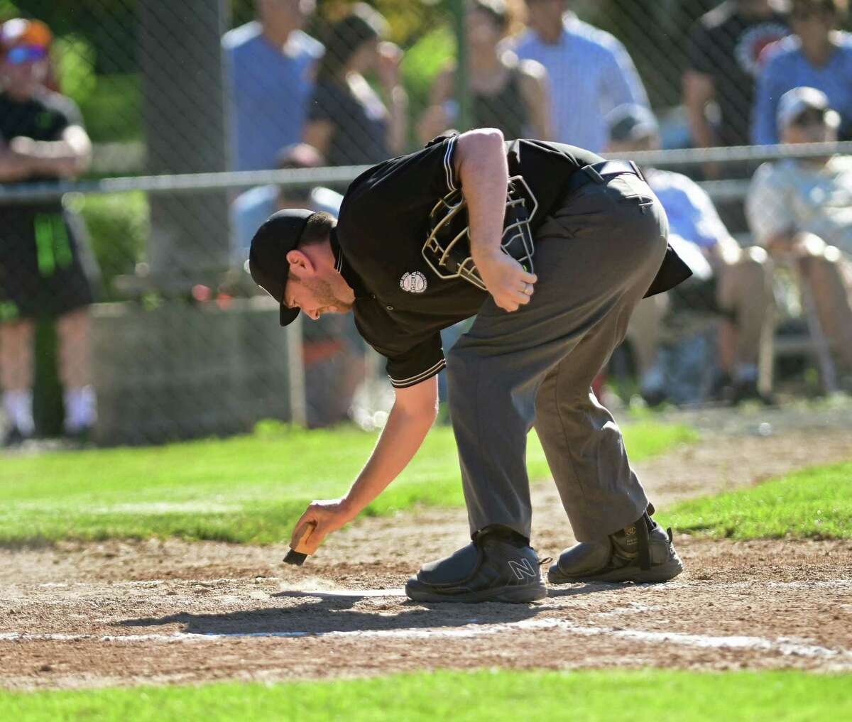 Home plate umpire Sean Ellott brushes off the dirt from home plate in between batters during a baseball game between Colonie and Columbia at Cook Park on Thursday, June 10, 2021 in Colonie, N.Y. (Lori Van Buren/Times Union)